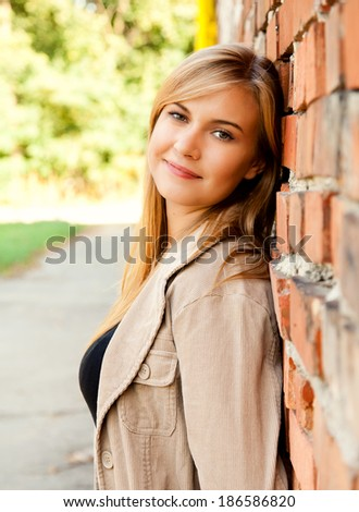 relaxation in the city, beautiful girl near brick wall, smiling
