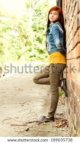 relaxation in the city, beautiful girl near brick wall, smiling, full lenght - stock photo