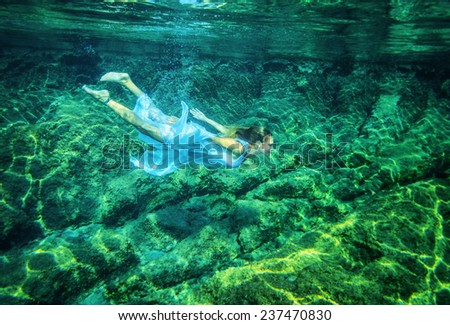 Relaxation in the sea, beautiful young female swimming underwater, summer time activity, refreshment and enjoyment concept