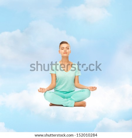 relaxation, meditation and lifestyle concept - girl on the cloud in lotus position and meditating - stock photo