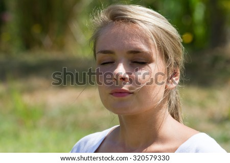 relaxation outdoors - thinking young woman closing her eyes,enjoying sun,green park background,summer daylight - stock photo