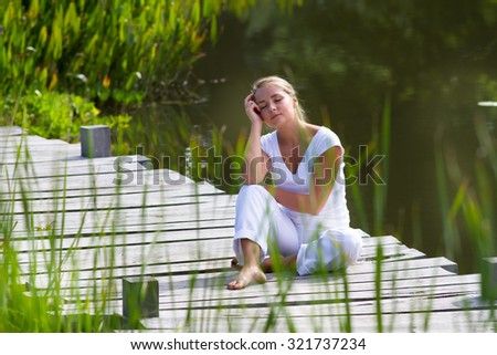 relaxation outside - daydreaming young woman enjoying relaxing herself,sitting on a wooden bridge, exotic water environment, summer daylight - stock photo