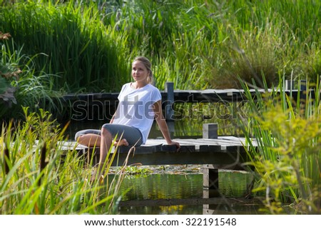 relaxation outside - smiling young woman enjoying putting her bare feet in water,sitting on a wooden bridge, green park environment, summer daylight - stock photo