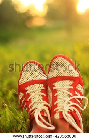 Relaxation. youth sneakers on girl legs on grass, sunny day, instagram look - stock photo