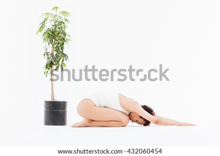 Relaxed african american young woman practicing yoga on the floor near small tree in pot over white background - stock photo