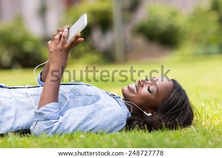 relaxed african woman lying on grass listening to music - stock photo