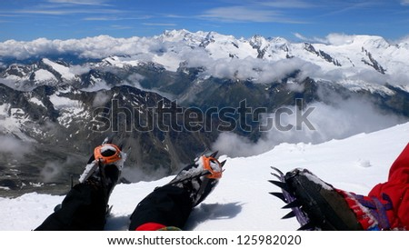 Relaxed and enjoying the views in Weissmies mountain's summit after a long climbing, the Alps, Switzerland - stock photo