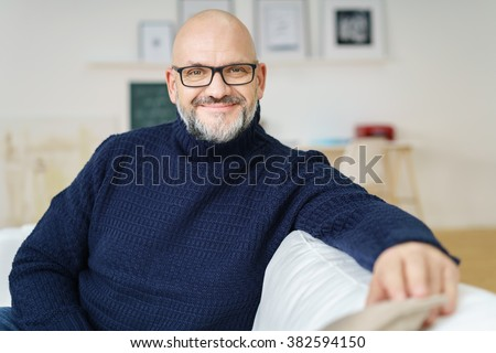 Relaxed attractive bald middle-aged man wearing glasses with a friendly smile sitting on a sofa in his living room smiling at the camera - stock photo