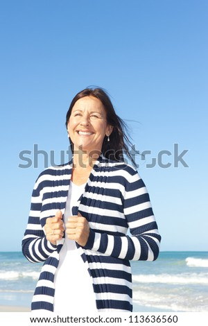 Relaxed attractive senior woman enjoying retirement at beach, isolated with ocean and blue sky as background and copy space. - stock photo