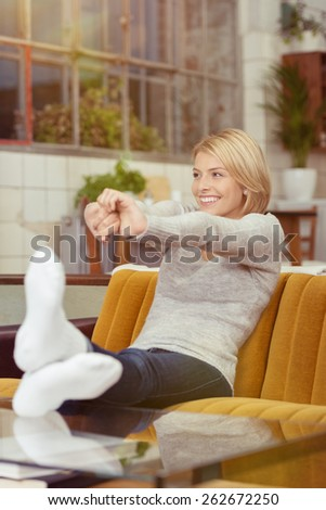 Relaxed attractive young woman stretching in contentment as she relaxes on a couch in the living room smiling with pleasure - stock photo