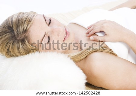 Relaxed beautiful blonde caucasian woman lying with closed eyes and resting her head over a fluffy white pillow - stock photo