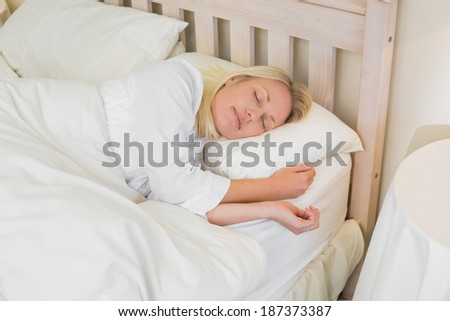 Relaxed beautiful woman sleeping in bed at home