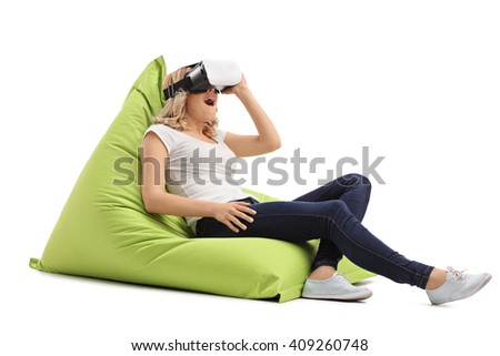 Relaxed blond girl using a VR goggles seated on a green beanbag isolated on white background