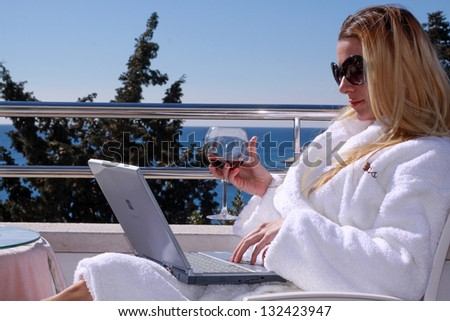 Relaxed blond woman holding glass with red vine in bathrobe clothes sitting on balcony with laptop and sea view