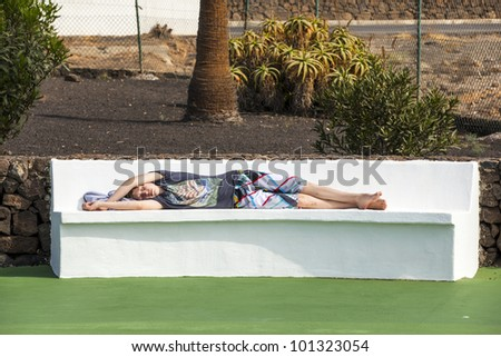 relaxed boy sleeping on the bench in the pool area - stock photo