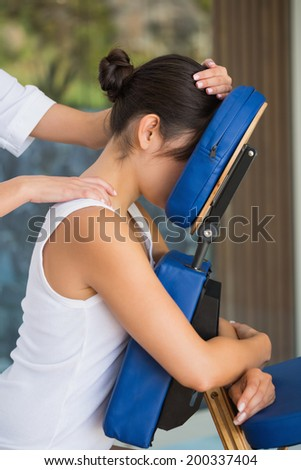 Relaxed brunette getting a massage in chair at the spa - stock photo