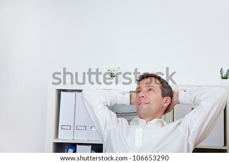 Relaxed business man leaning back in his office - stock photo