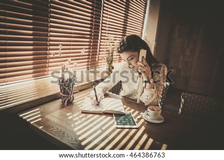 Relaxed business woman making phone call and writing in her notebook
