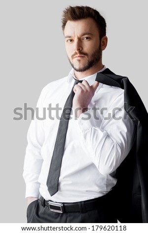 Relaxed businessman. Handsome young man in formalwear holding his jacket on finger and looking at camera while standing against grey background - stock photo