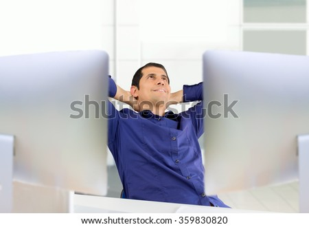 relaxed businessman in office on his dual desktop screens - stock photo