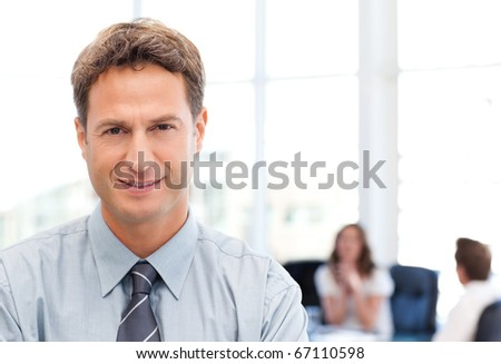 Relaxed businessman posing in front of his team while working in the background - stock photo