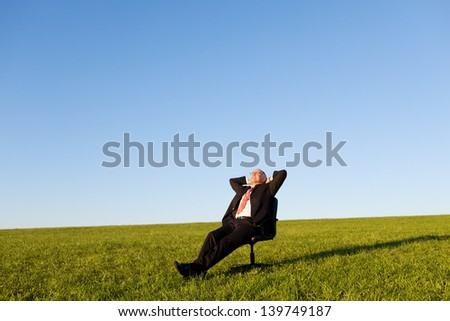 Relaxed businessman sitting on green grassland under blue sky