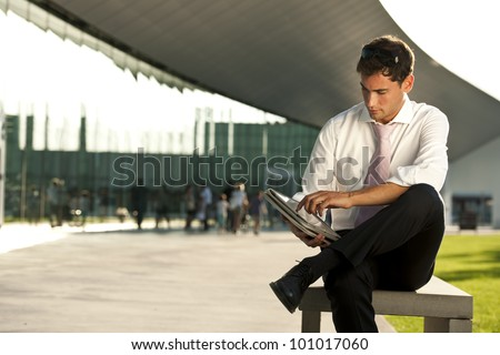 Relaxed businessman using his PC tablet while sitting on a bench - stock photo