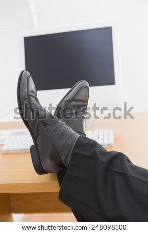 Relaxed businessman with his feet up in his office - stock photo