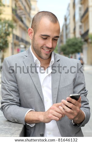 Relaxed businessman with mobile phone in town - stock photo