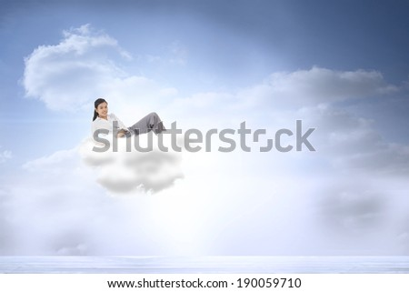Relaxed businesswoman lying against beautiful blue sky with clouds