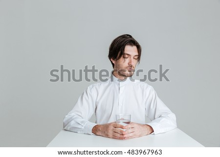 Relaxed calm young man holding water glass while sitting at the table isolated on the gray background