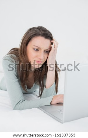 Relaxed casual sad young woman using laptop in bed at home