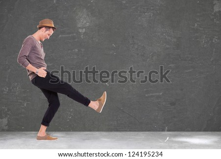 relaxed casual young man kicking and smiling - stock photo