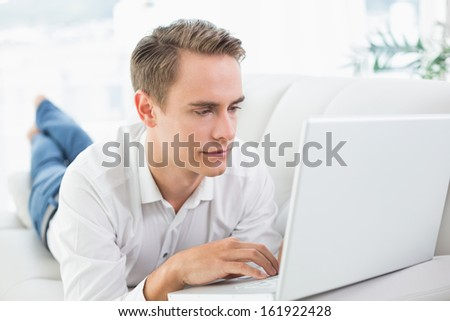 Relaxed casual young man using laptop while lying on sofa in a bright house