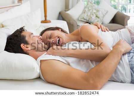Relaxed cheerful young couple lying together in bed at home - stock photo