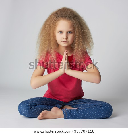 Relaxed child practicing yoga isolated on white background. little girl does yoga - stock photo