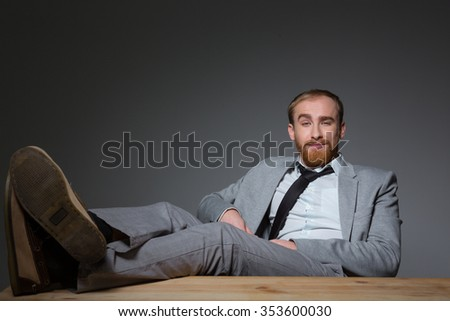 Relaxed confident business man in grey suit sitting with legs on table over grey background - stock photo