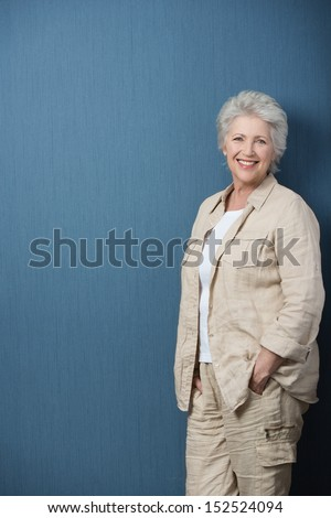 Relaxed confident senior teacher or businesswoman in stylish modern clothes standing against a blank green chalkboard - stock photo