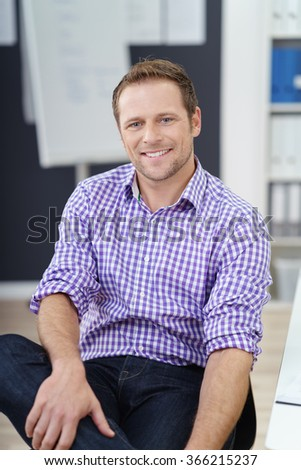 Relaxed confident young businessman in an informal office sitting back in his chair smiling at the camera