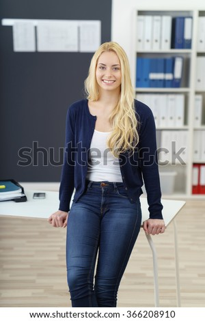 Relaxed confident young businesswoman in jeans standing perched on the edge of an office table beaming happily at the camera