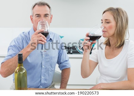 Relaxed couple drinking wine in the kitchen at home