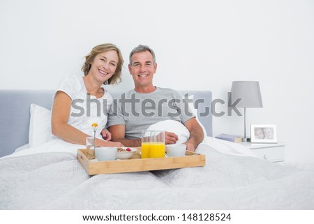 Relaxed couple having breakfast in bed together smiling at camera at home in bedroom - stock photo