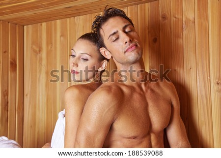 Relaxed couple in hotel sauna leaning on each other - stock photo