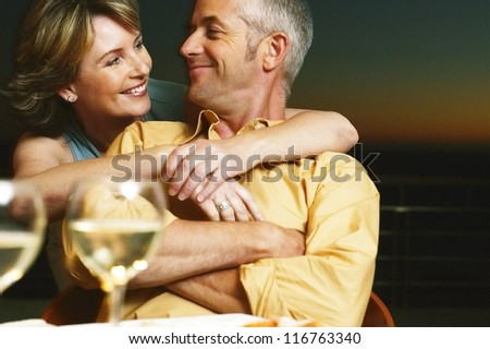 Relaxed couple sitting enjoying a glass of wine together share a special moment of affection and love - stock photo