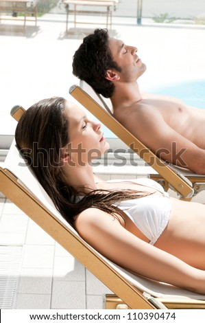 Relaxed couple sunbathing together at swimming pool in summer - stock photo