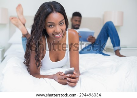 Relaxed couple using technology on bed at home in bedroom - stock photo