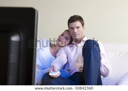 Relaxed couple watching TV, selective focus - stock photo