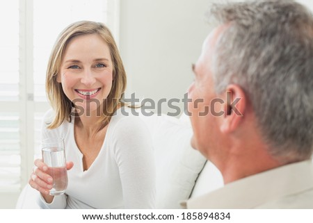 Relaxed couple with a glass of water in living room at home