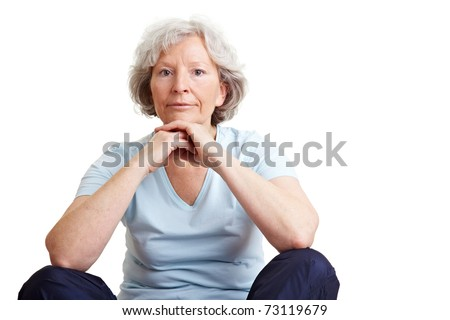 Relaxed elderly woman sitting in tailor seat on the floor - stock photo