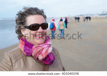 Relaxed elderly woman walking on the beach - Senior woman wearing scarf and sunglasses - Blue sky - stock photo